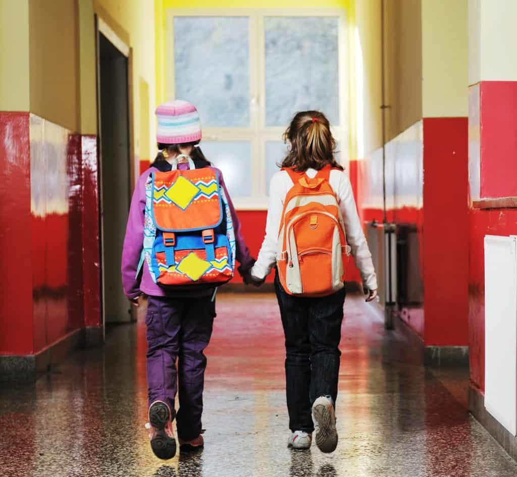 Happy two girls walking indoor at school hall - managing diabetes in school