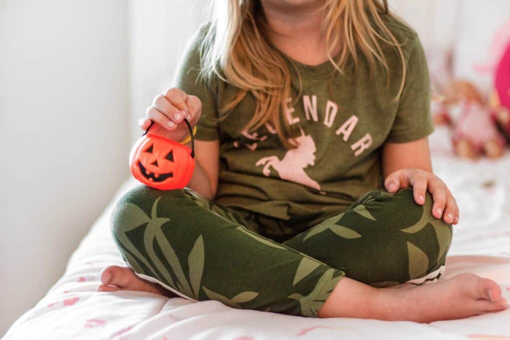 girl on bed with small halloween basket